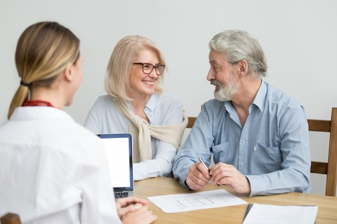 a senior couple talking with a doctor about options for treatment