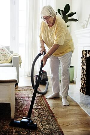 elderly woman vacuuming