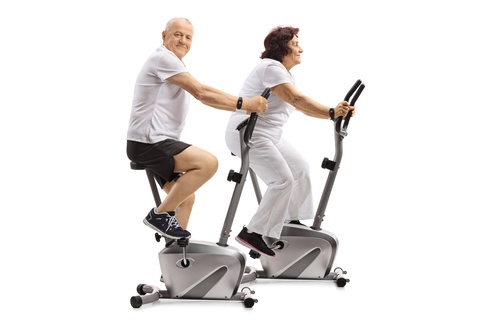elderly couple riding stationary bikes