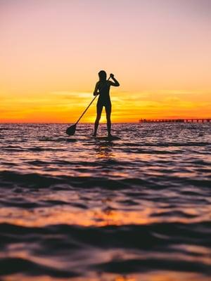 paddle boarding at dusk