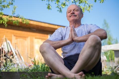 senior man meditating in the park