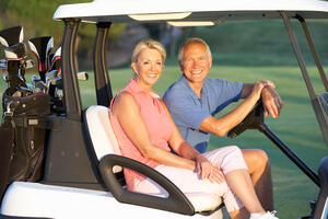 elderly couple riding a golf cart