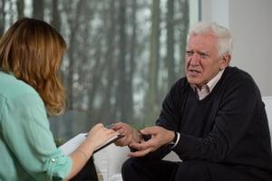 elderly man speaking with a therapist