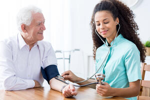 Doctor taking senior patients' blood pressure