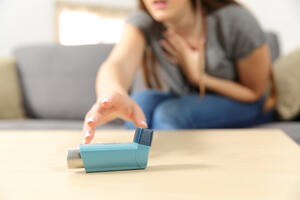 women reaching for asthma inhaler